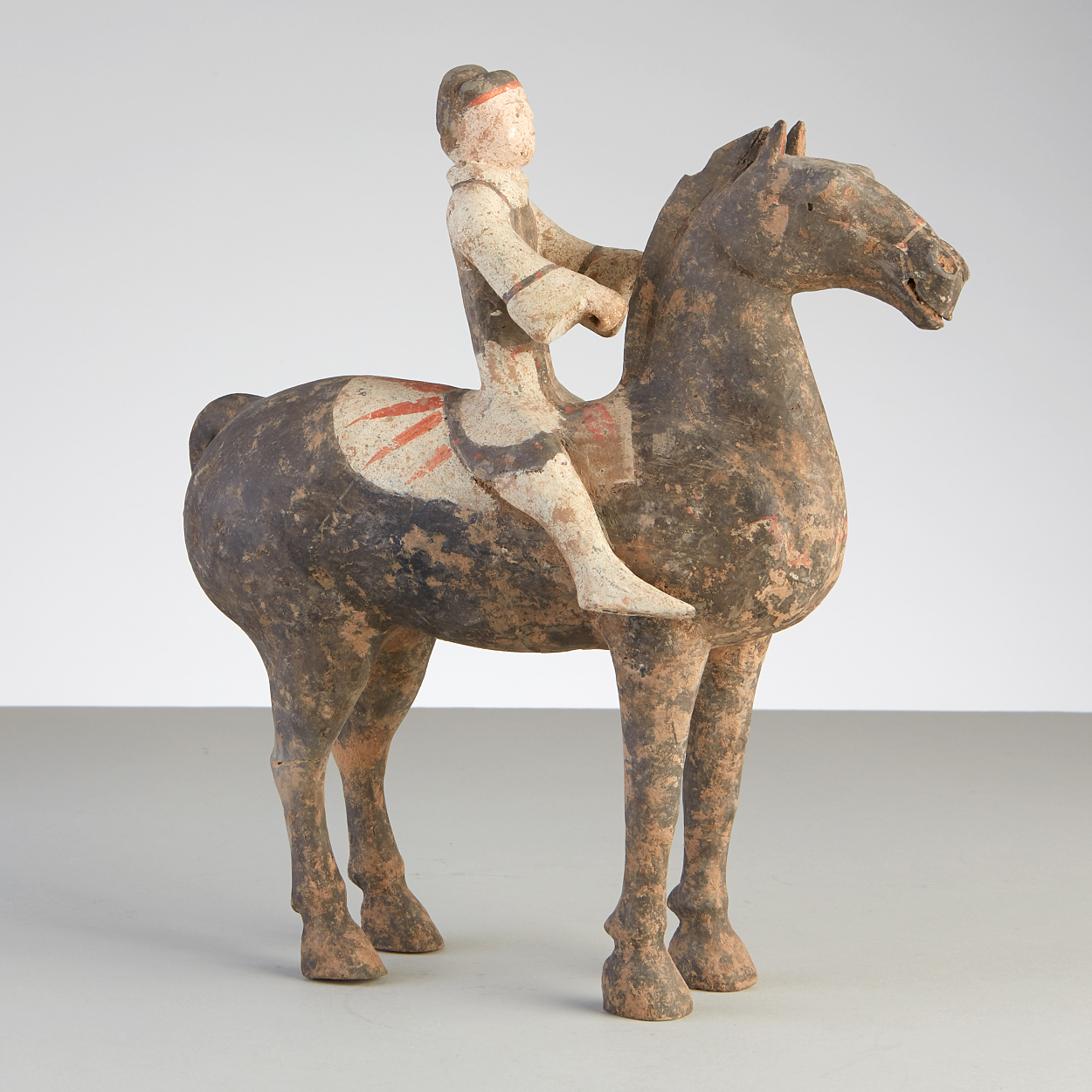 A Painted Grey Pottery Model of a Horse and Rider
